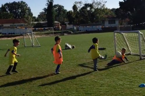 Goalkeeper hit in the face by shot in children's training game
