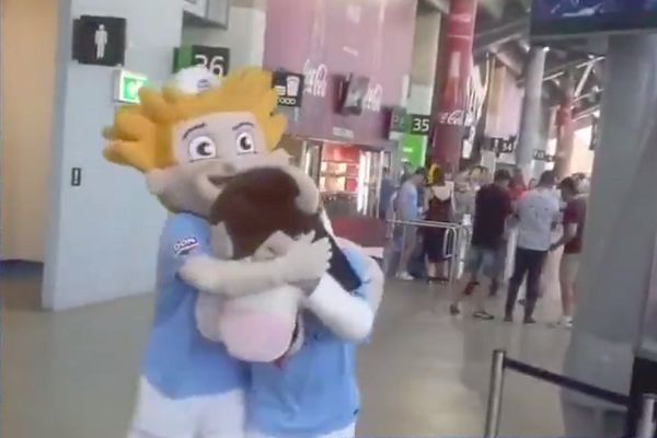 Melbourne City sailor mascot hides the bull mascot's eyes from a stall selling roast beef