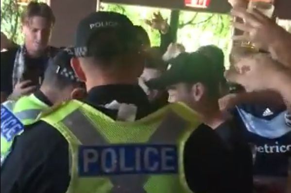 Melbourne Victory supporters watch police searching one fan for flares