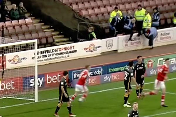 A steward falls over the advertising hoardings after a goal in Barnsley vs Bradford