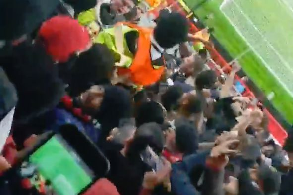 Man Utd steward is picked up by PSG fans at Old Trafford during a Champions League win for the French side