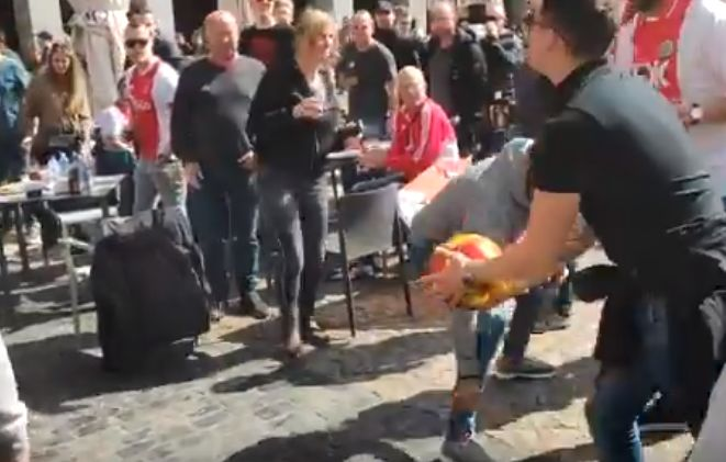An Ajax fan hits a Real Madrid flag on a balcony with a ball in the Plaza Mayor