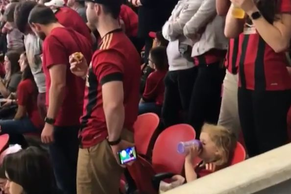 Atlanta fan at game against Cincinnati holds a phone behind his back for a child to watch