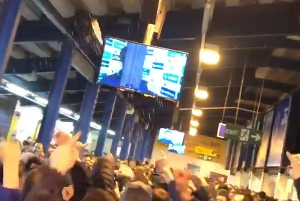 An Everton fan's drink hits the screen as Jürgen Klopp appears on it before the Merseyside derby at Goodison Park