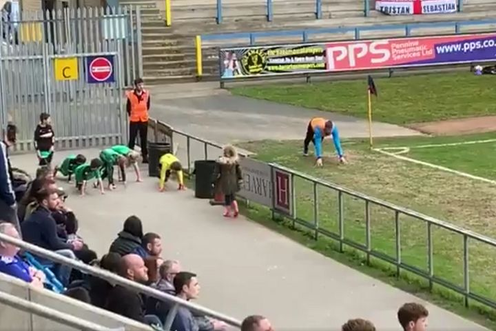 Children warm-up next to Halifax substitute Scott Quigley during 2-0 win over Solihull Moors