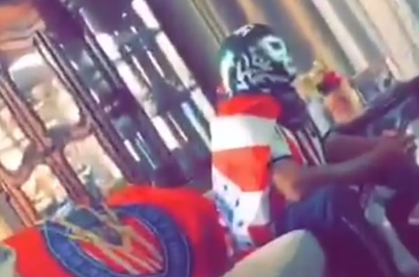 Chivas fan watches their 2-0 Copa MX quarter-final defeat at Club América from home while wearing a shirt and a mask
