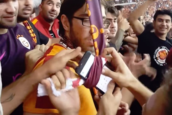 Galatasaray fans tie a dropped phone to the end of a length of scarves tied together before pulling it back to its owner in the upper tier