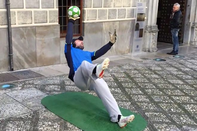 Street artist is living statue of goalkeeper making save