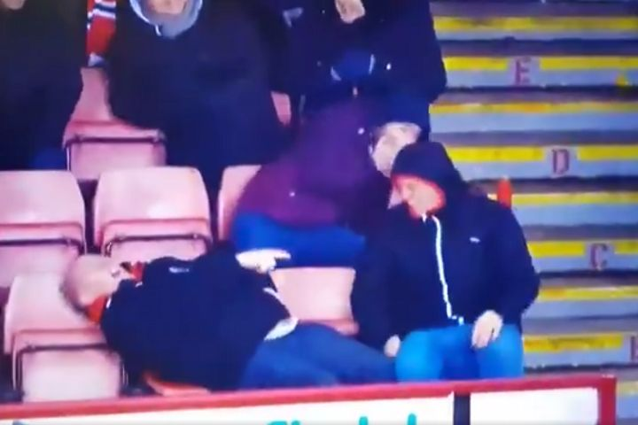 A Sheffield United fan fell over as he was kicking the ball back onto the pitch during a game with Brentford