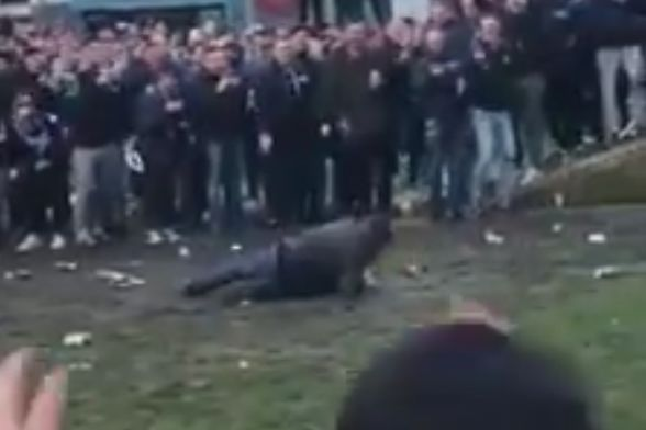 A Schalke fan slips over in the mud while playing football in Manchester