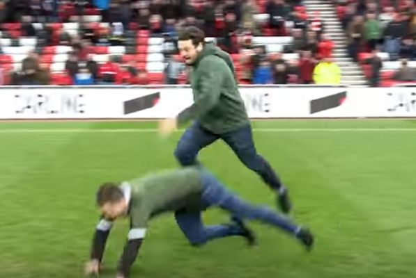 A Sunderland fan trips his Plymouth counterpart during a half-time race at the Stadium of Light