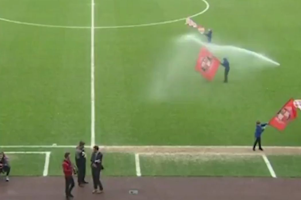 A flag waver is sprayed by a sprinkler at Sunderland vs Walsall in the Stadium of Light