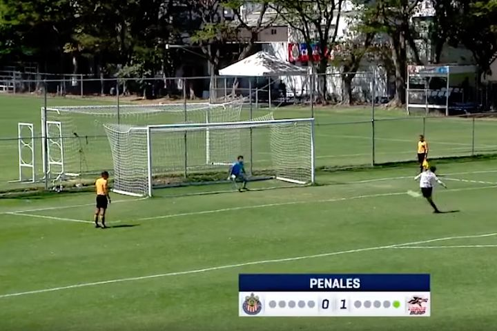 A Chivas Under-17 player scores a penalty against Lobos BUAP after the ball hits the crossbar but then unexpectedly goes in