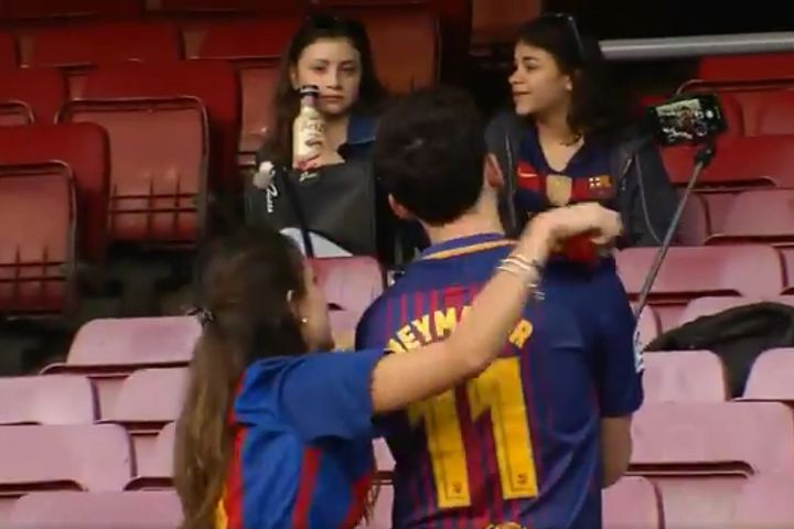 Couple of Barcelona fans take selfies together at the Nou Camp