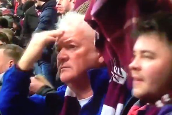 A Hearts fan blesses himself after making an obscene gesture towards Hibernian supporters at the Edinburgh derby