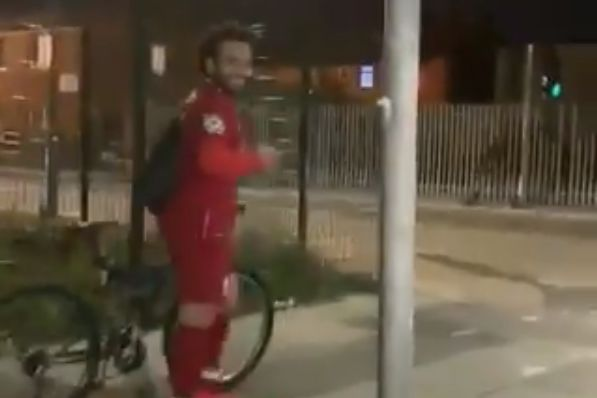 Mohamed Salah lookalike in full kit pushes a bicycle along the pavement in Liverpool