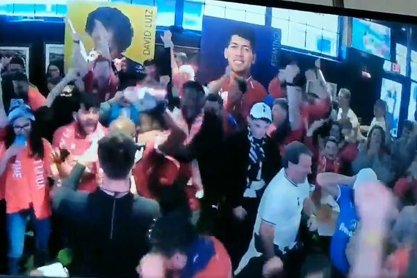 Spurs fan is surrounded by celebrating Liverpool supporters in a fan zone in America after their late winning goal
