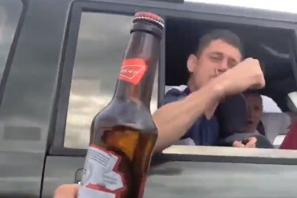 Liverpool fans pass a bottle of beer between cars driving to Madrid on their way to the Champions League final