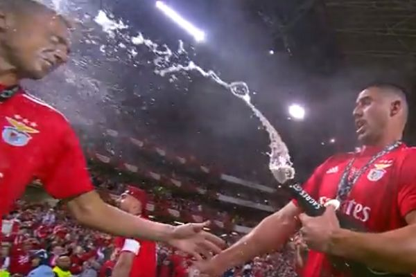 Gabriel Appelt Pires opens a bottle of champagne in Odisseas Vlachodimos's face during Benfica title celebrations