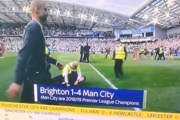 Man City manager Pep Guardiola walks past stewards holding down a pitch invader after his team won 4-1 at Brighton to win the Premier League title