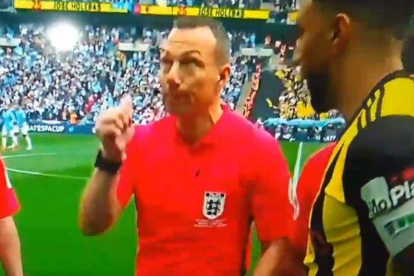Referee Kevin Friend flicks a coin over his head accidentally during the toss before Man City v Watford in the FA Cup final