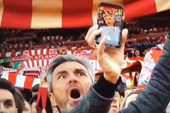 Liverpool fan holds his phone the wrong way round trying to take a selfie at Anfield for the Champions League win over Barcelona
