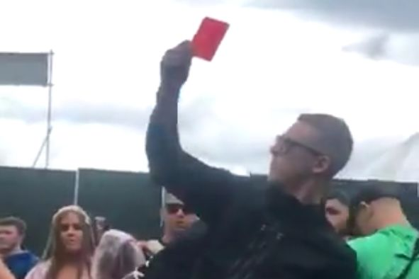 Raver dances with a football referee's yellow and red cards at Parklife Festival