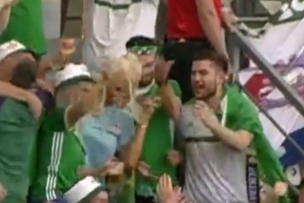 A travelling Northern Ireland fan gets a beer spilled in his face during goal celebrations in Estonia