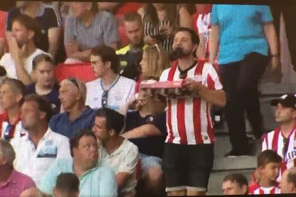 PSV fan drinks while holding a tray with both hands in the aisles at a Champions League qualifier against Basel