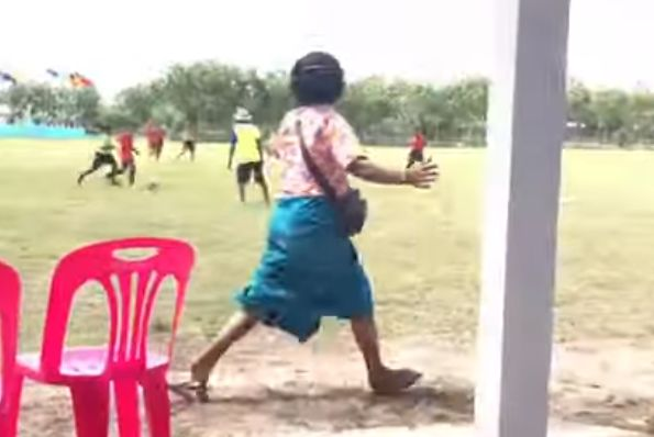 Thai grandmother cheers on her grandchild from the sidelines during a match