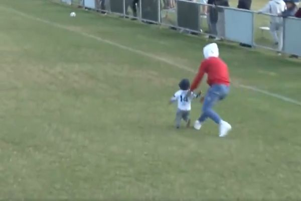 Young child runs on the pitch during Coomera Colts vs Surfers Paradise Apollo