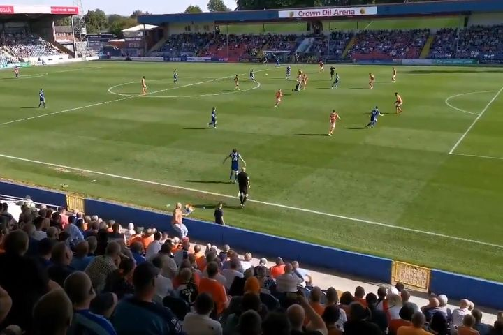 Blackpool fan with Pride flag runs behind assistant referee at Rochdale