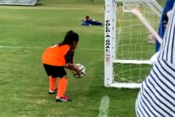 Young girls picks up ball to have another shot after her first shot goes wide