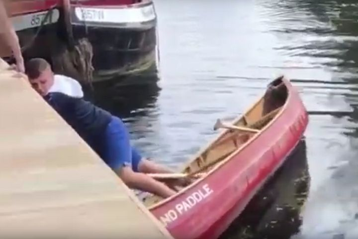 Newcastle fan clings on to the side after getting his feet stuck in a boat in Norwich