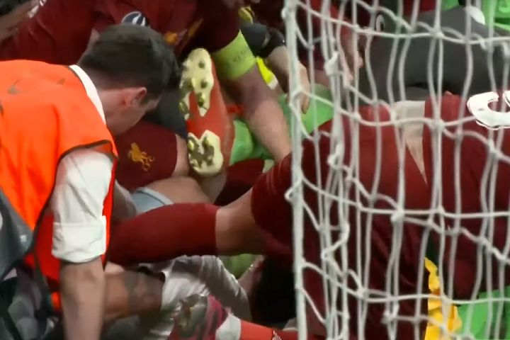Pitch invader slides into the Liverpool players after they won the Super Cup on penalties, injuring goalkeeper Adrián