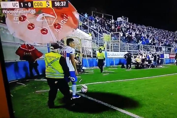 A man holds an umbrella to stop missiles hitting the Universidad Católica corner taker during a 1-1 draw with Coquimbo Unido in the Chilean Primera División