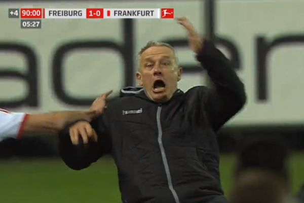 Freiburg manager Christian Streich falls over following David Abraham's shoulder barge