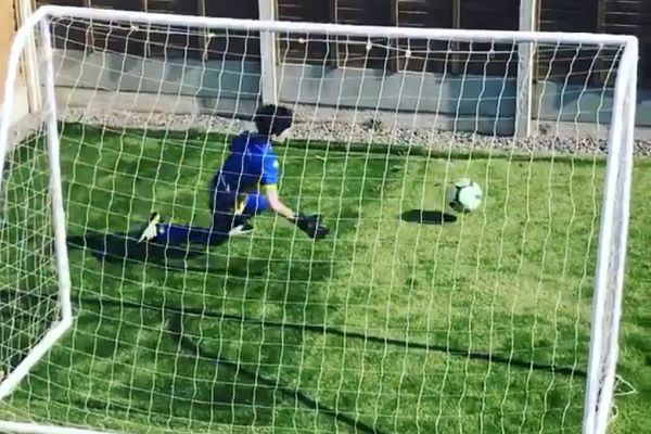 A young goalkeeper takes shots against himself during coronavirus isolation with the help of a fence in his garden