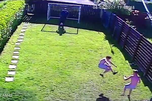 Boy attacks brother after bad tackle while playing football in the garden with their dad