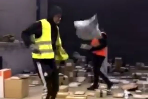 Employee does kick ups with delivery package at sorting centre