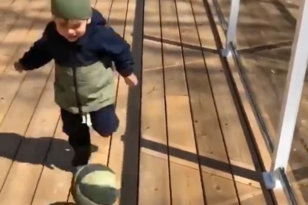 Child falls over ball in kickabout during lockdown on garden decking