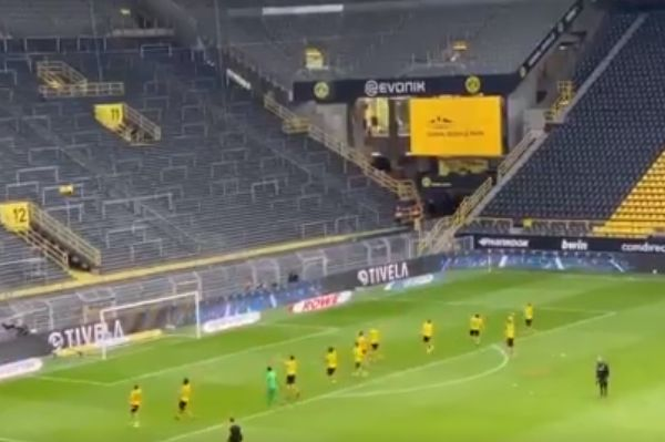 Borussia Dortmund players celebrate in front of an empty Südtribüne stand after beating Schalke 4-0 behind closed doors