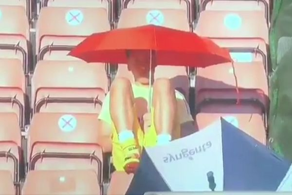 Mesut Ozil holds an umbrellas to shield himself from the sun at Southampton