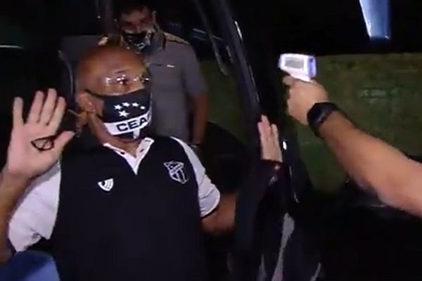 Ceará coach André Luís dos Santos raises hands in response to temperature check before game at Fortaleza
