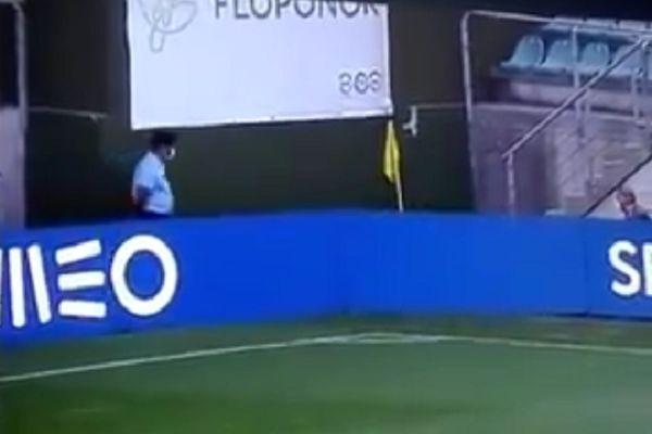 Staff member retrieving corner flag falls over advertising boards at Tondela