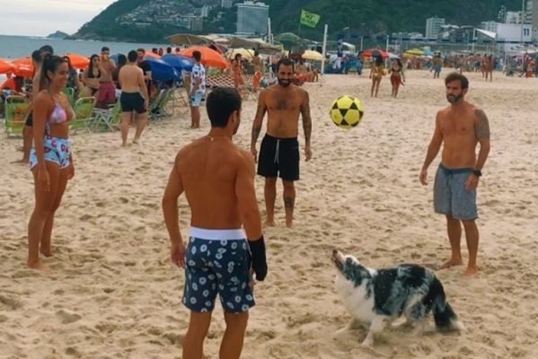Dog joins in with keepie uppies games on beach in Brazil