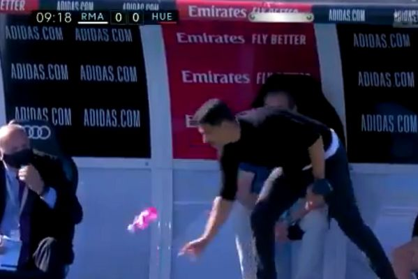Huesca manager Míchel tries to flip a bottle onto its bottom during La Liga defeat to Real Madrid