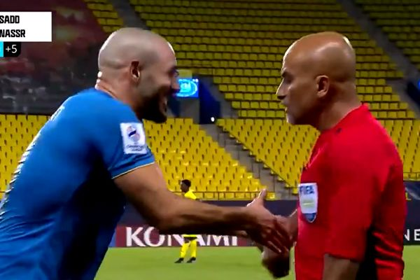 Al-Nassr's Nordin Amrabat laughs while thanking linesman for wrong offside call at Al Sadd