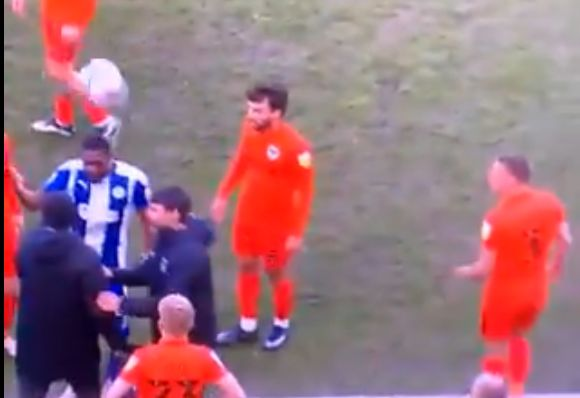 Lee Brown throws a ball onto Tendayi Darikwa's head during touchline row at Wigan vs Portsmouth