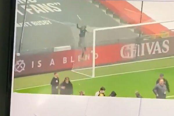 Man Utd fan falls off net on top of goal when shot is taken